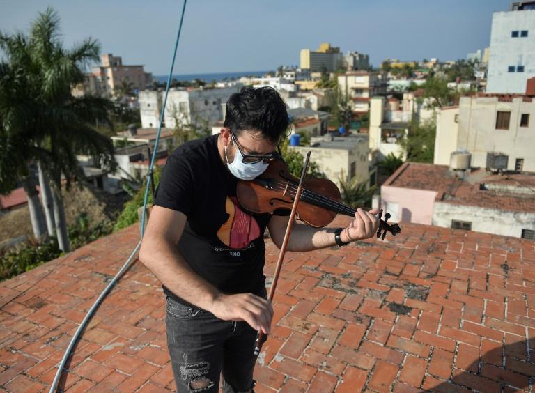 William Roblejo joue du violon sur le toit de sa maison, le 15 avril 2020 à La Havane, à Cuba