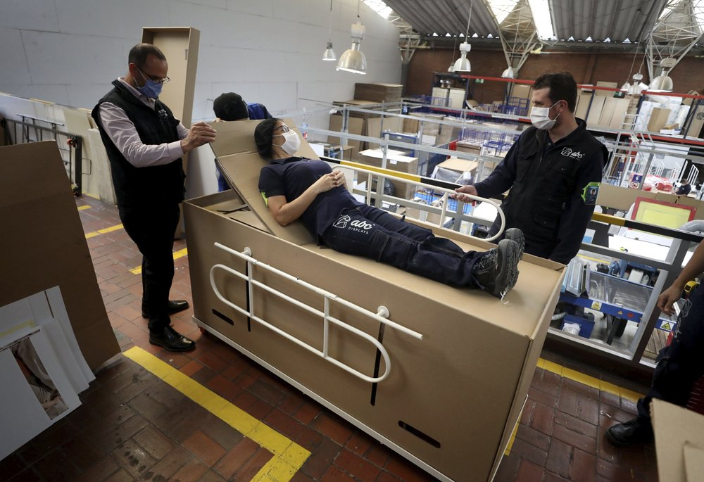 Rodolfo Gomez (left) and his employees demonstrate how their design of a cardboard box can serve as both a hospital bed and a coffin designed for COVID-19 patients, in Bogota, Colombia on Friday, May 8. (AP Photo/Fernando Vergara)