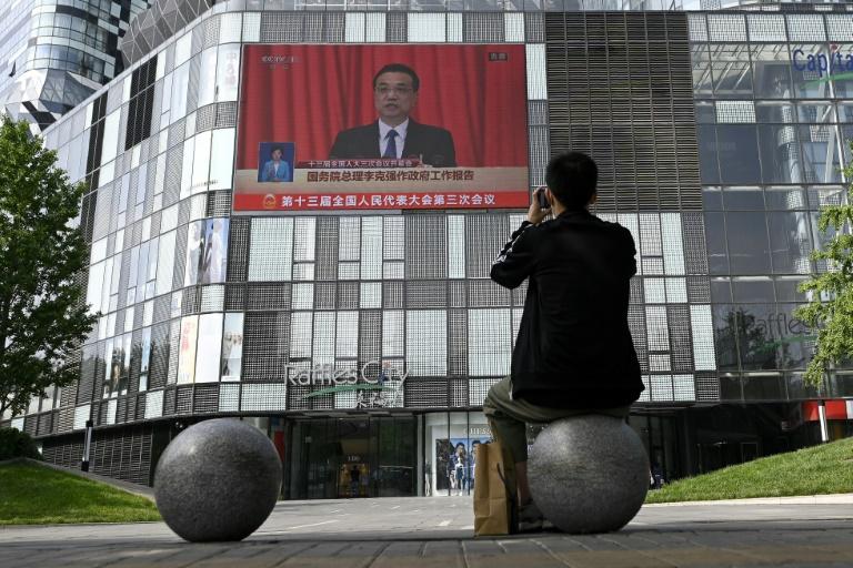 Un Chinois regarde sur un écran géant la session inaugurale du parlement chinois, le 22 mai 2020 dans une rue de Pékin