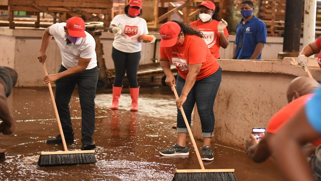 Digicel Foundation and Kingston and St Andrew Municipal Corporation team members scrub the floor of the Coronation Market in downtown Kingston on Labour Day. (Photos: Marlon Reid)