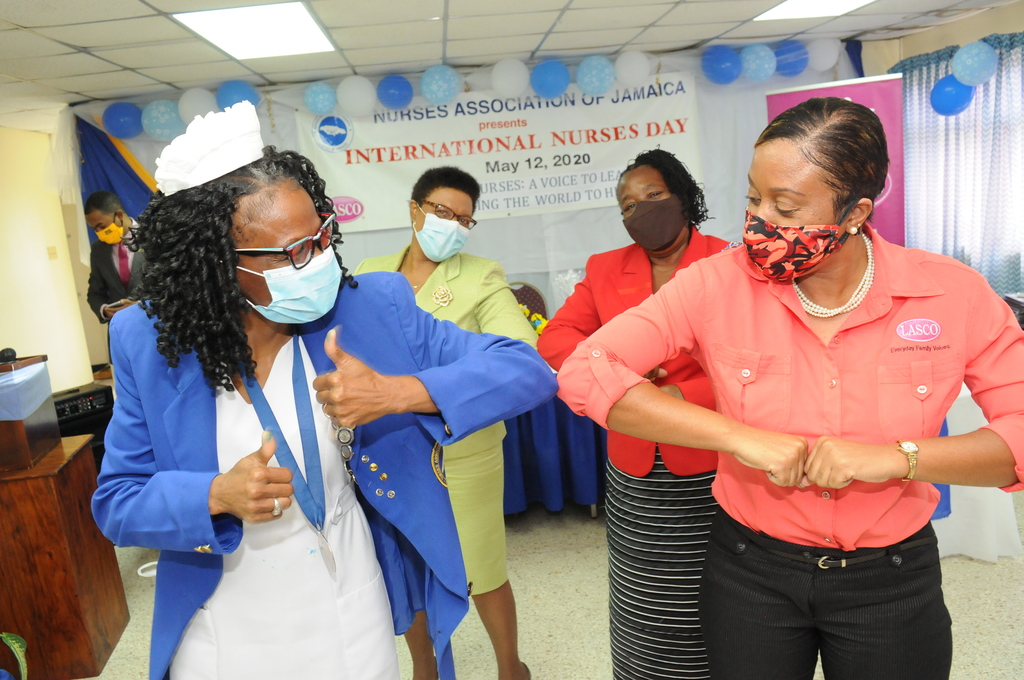 Renee Rose (right), corporate programmes manager at LASCO Distributors Limited and Carmen L. Johnson (left), president of the Nurses Association of Jamaica salute nurses on International Nurses Day during a commemoration service at the NAJ Headquarters in Kingston.