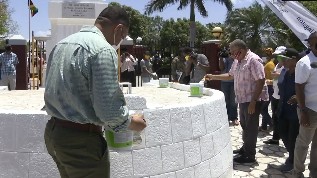 Prime Minister Andrew Holness and Opposition Leader Dr Peter Phillips paint around the statue of Sir Alexander Bustamante at the St William Grant Park in downtown Kingston on Monday.
