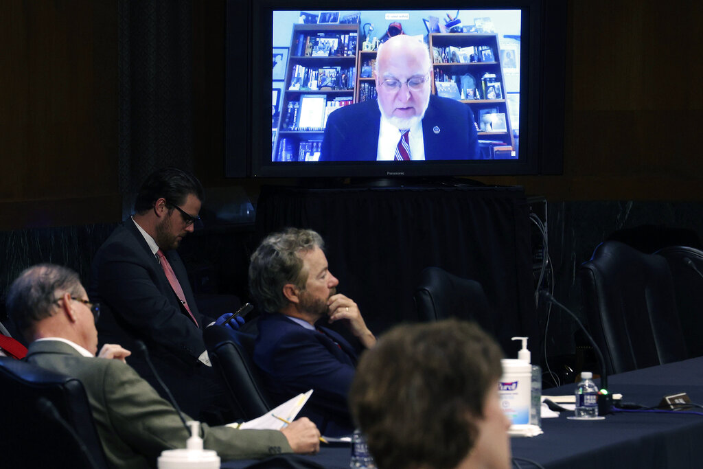 Senators and staff listen to Dr Robert Redfield, director of the Centers for Disease Control and Prevention, speak remotely during a virtual Senate Committee for Health, Education, Labor, and Pensions hearing, Tuesday, May 12, 2020, on Capitol Hill in Washington. (Win McNamee/Pool via AP)