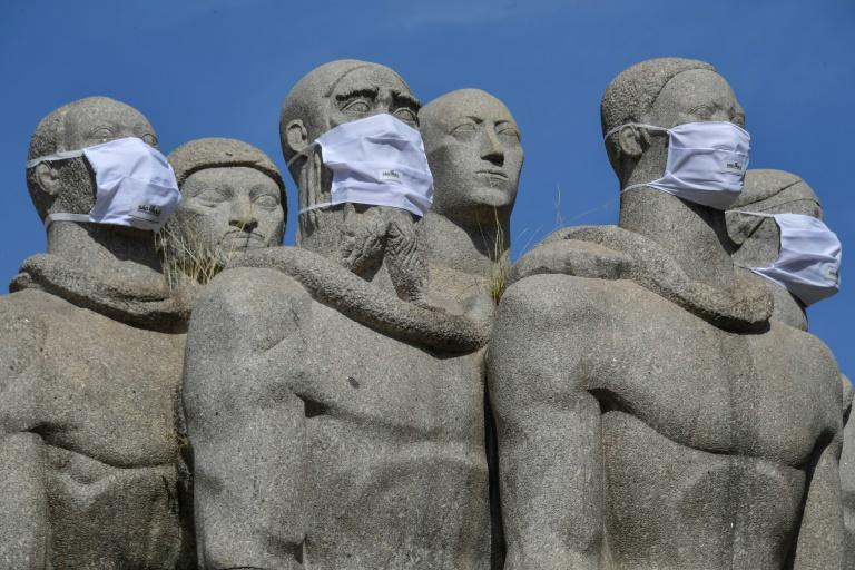 Les statues du Monument aux drapeaux, à Sao Paulo, au Brésil, munies de masques de protection contre le coronavirus, le 12 mai 2020