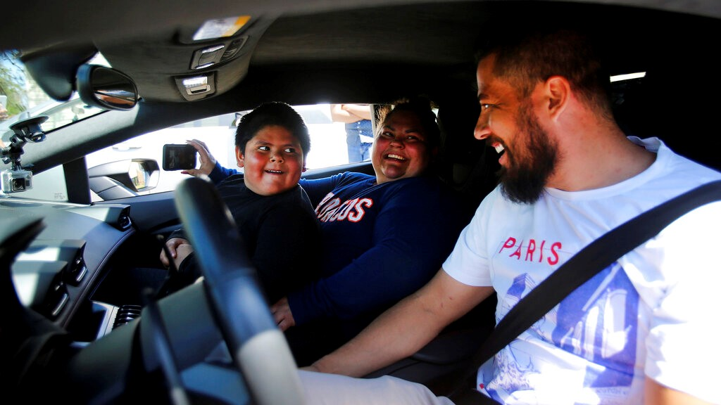 Adrian Zamarripa reacts after Adrian and his mother, Beatriz Flores, went for a ride in Jeremy Neves' Lamborghini Huracan in Ogden, Utah, Tuesday, May 5, 2020. (Scott G Winterton/The Deseret News via AP)