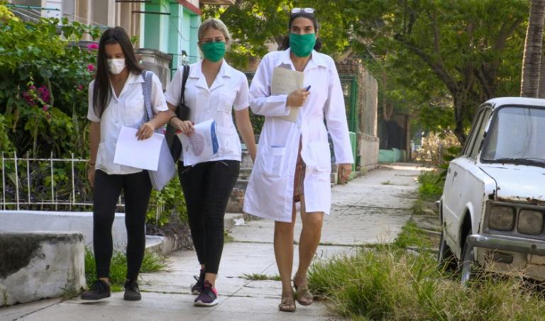 La docteure cubaine Liz Caballero (d) fait du porte-à-porte avec des étudiantes, en quête de nouveaux cas de coronavirus,le 31 mars 2020 à La Havane