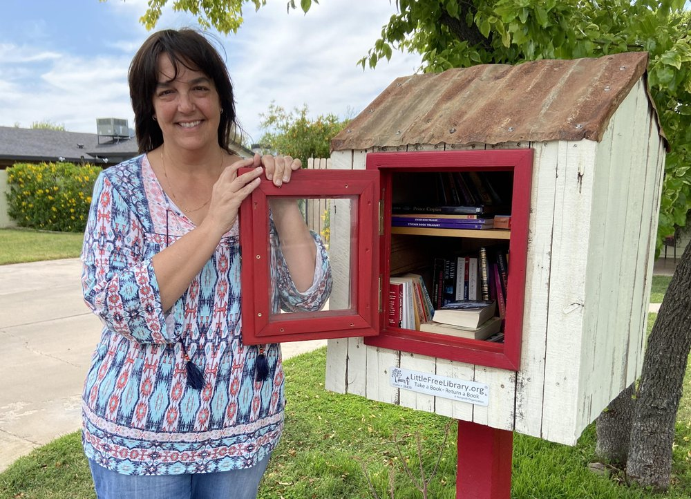 Kerri Kaplan, a fifth grade teacher, stands next to a small library she has in her front yard in Phoenix, Arizona. As government orders shuttered public libraries to slow the spread of coronavirus, some have turned to official and unofficial book-sharing means to satisfy their desire for new reading material. (AP Photo/Michelle A Monroe)