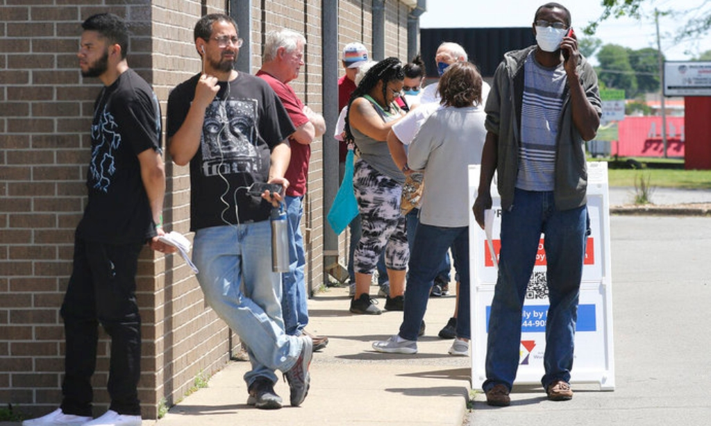 In this April 30, 2020 photo, people wait outside of the at the Arkansas Workforce Center as the line wraps around the building in Jacksonville, Ark. (Thomas Metthe/ Arkansas Democrat-Gazette via AP)
