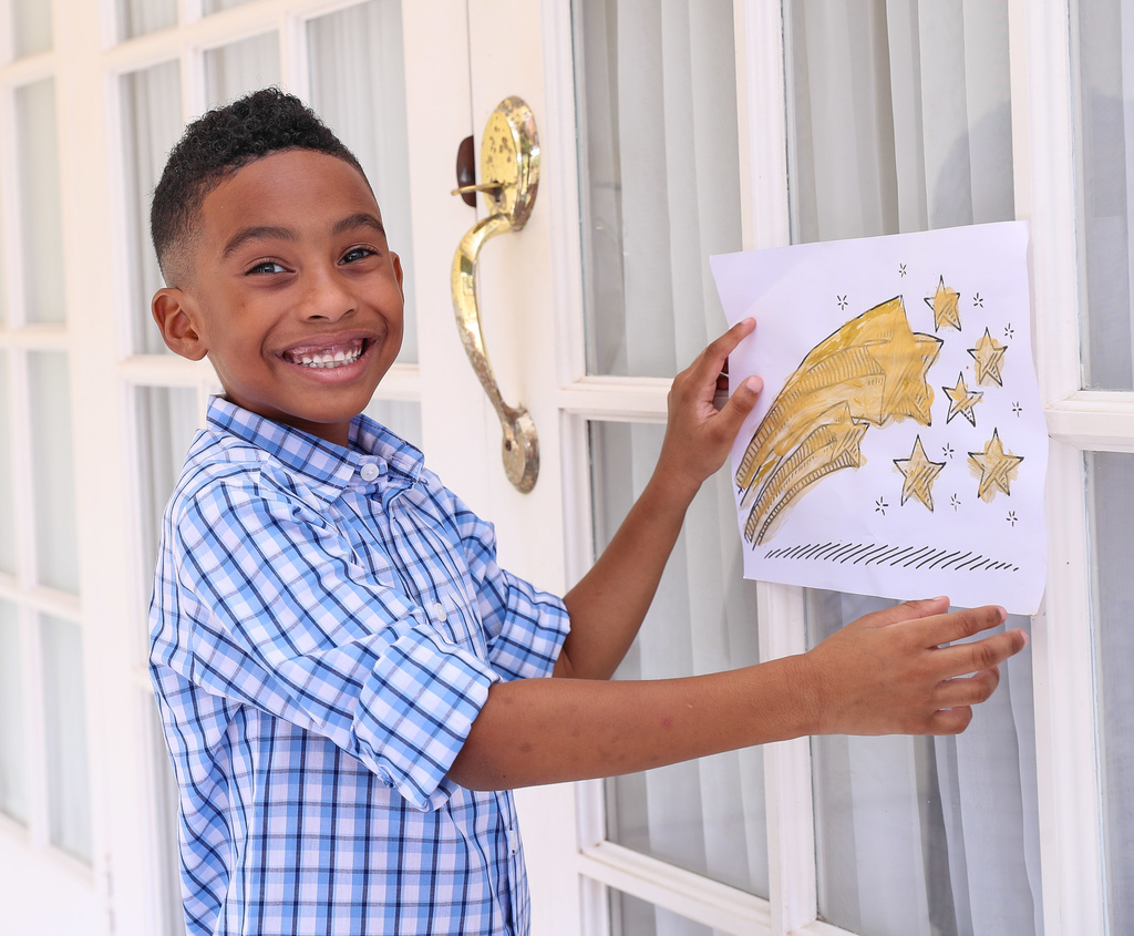 Kaleb Robinson shows his painted shooting star affixed to the front door at his home, as he participates in the Sagicor Bank Brighter Future campaign to inspire hope amidst the COVID-19 pandemic.