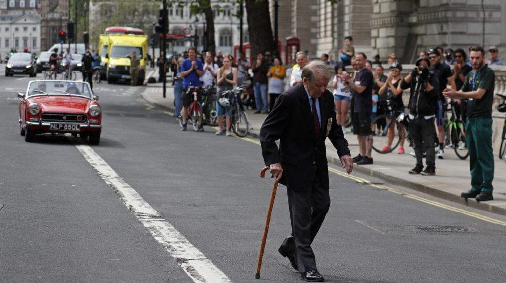 People applaud as a WWII veteran walks past after two minutes of silence was observed in Whitehall in London, Friday, May 8, 2020, on the 75th anniversary of the end of World War II in Europe. (AP Photo/Frank Augstein)