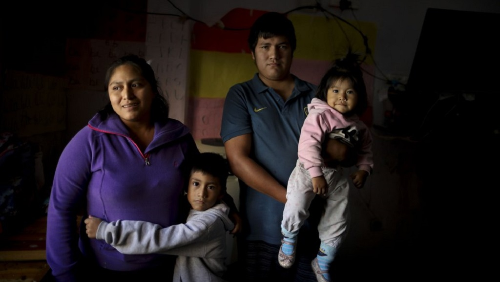 In this April 7, 2020, photo, Rosemary Paez Carabajal, left, her husband Yonoma Saenz, their children Laisa and Leonardo pose for a photo at the room they rent in Buenos Aires, Argentina. Carabajal makes a living selling coffee on the street, and can no longer do her job after the government-ordered lockdown to curb the spread of the new coronavirus. (AP Photo/Natacha Pisarenko)
