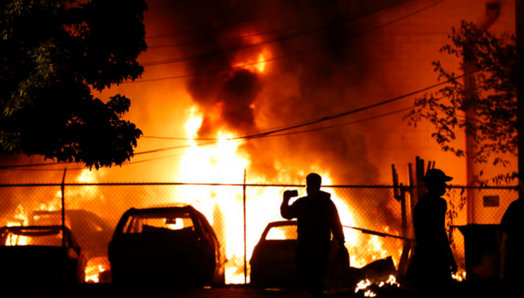 People watch a fire Friday, May 29, 2020, in Minneapolis. (AP Photo/Julio Cortez)