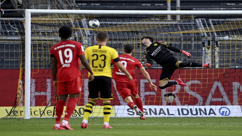 Dortmund's goalkeeper Roman Buerki, right, fails to safe a shot by Munich's Joshua Kimmich during the German Bundesliga football match against FC Bayern Munich in Dortmund, Germany, Tuesday, May 26, 2020. The German Bundesliga is the world's first major football league to resume after a two-month suspension because of the coronavirus pandemic. (Federico Gambarini/DPA via AP, Pool).