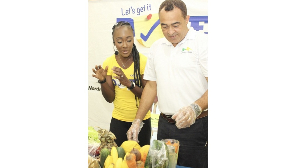 Certified nutrition health coach and personal fitness trainer, Meisha-Gay Mattis, demonstrates the preparation of  smoothies to Health Minister Dr Christopher Tufton at the Courts Let's Get it Done 2018 workshop.