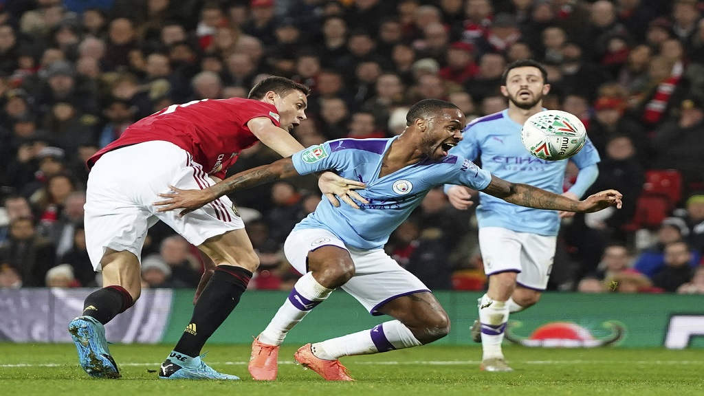 Manchester United's Nemanja Matić, centre, holds back Manchester City's Raheem Sterling who falls during the English League Cup semifinal first leg football match at Old Trafford, Manchester, England, Tuesday, Jan. 7, 2020. (AP Photo/Jon Super).