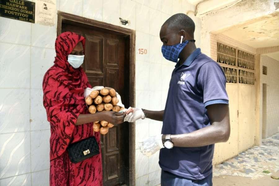 Mohammed François Mané, un employé de la start-up Paps, livre des baguettes de pain à Dakar, le 30 avril 2020. afp.com - Seyllou