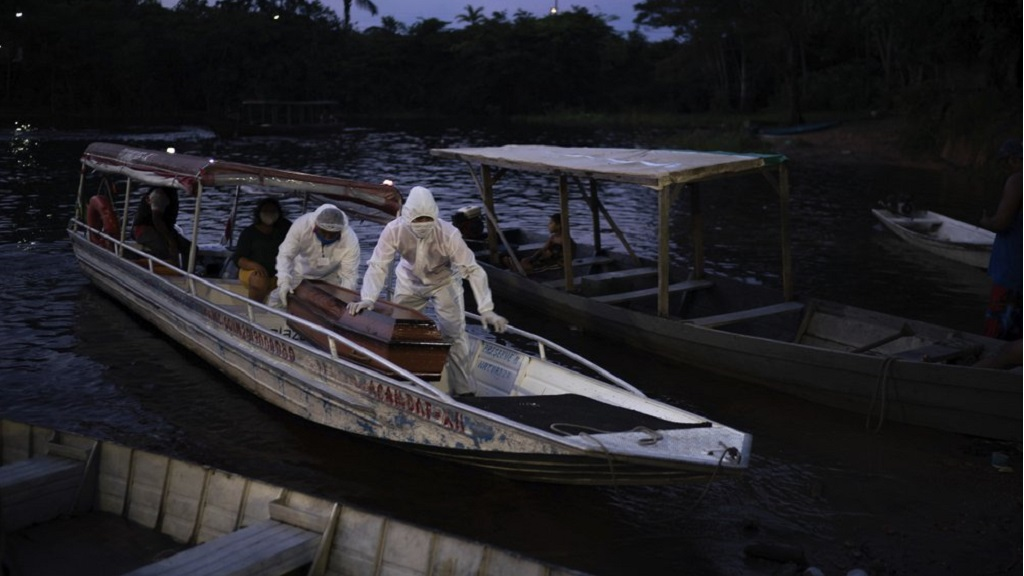 SOS Funeral workers transport by boat a coffin carrying the body of an 86-year-old woman who lived by the Negro River and is a suspected to have died of COVID-19, near Manaus, Brazil, Thursday, May 14, 2020. The virus has spread upriver from Manaus, creeping into remote riverside towns and indigenous territories to infect indigenous tribes. (AP Photo/Felipe Dana)