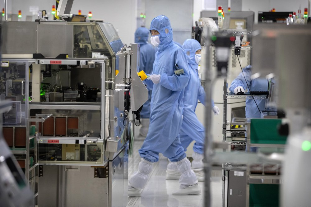 Employees wearing protective equipment work at a semiconductor production facility for Renesas Electronics during a government organized tour for journalists in Beijing, Thursday, May 14, 2020. China reported three new coronavirus cases Thursday while moving to reopen for business and schools. (AP Photo/Mark Schiefelbein)