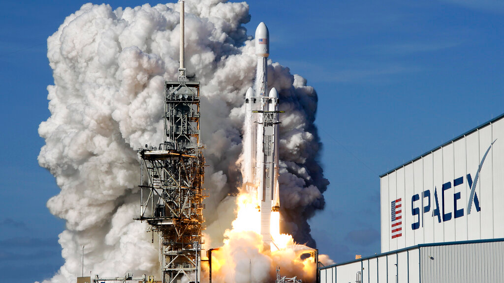 FILE - In this Tuesday, Feb. 6, 2018 file photo, a Falcon 9 SpaceX heavy rocket lifts off from pad 39A at the Kennedy Space Center in Cape Canaveral, Fla. The Falcon Heavy, has three first-stage boosters, strapped together with 27 engines in all.
