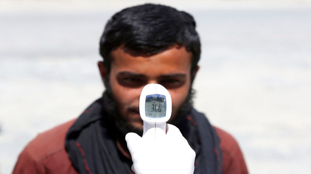 A health worker checks the temperature of car passengers in an effort to help stop the spread of the coronavirus, as they enter the city in the Paghman district of Kabul, Afghanistan, Sunday, May 3, 2020. (AP Photo/Rahmat Gul)