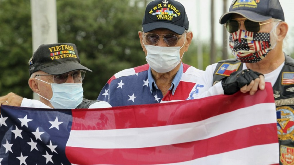 Tom Springer, Col. Frank Plummer and Hal Jones hold an American flag during Memorial Day ceremonies at the American Spire Plaza of Honor in McAllen, Texas, Monday, May 25, 2020. (Delcia Lopez/The Monitor via AP)