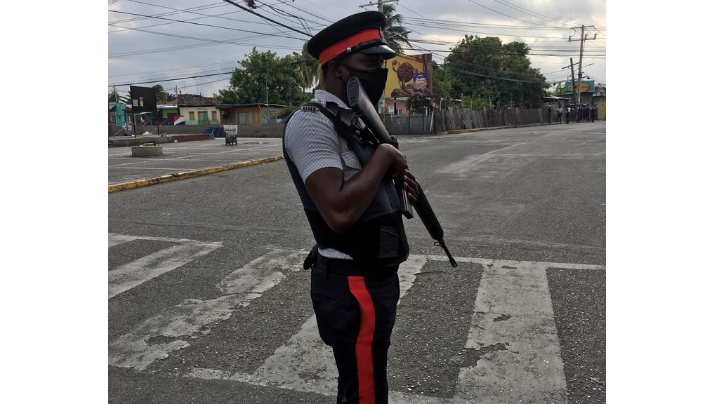 A policeman stands guard in Spanish Town, St Catherine as the curfew took effect in the old capital on Easter Monday. (Photos: Lynford Limpson)