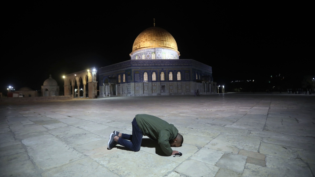 A muslim man pray next to the Dome of the Rock Mosque in the Al Aqsa Mosque compound in Jerusalem's old city, Sunday, May 31, 2020.The Al-Aqsa mosque in Jerusalem, the third holiest site in Islam, reopened early Sunday, following weeks of closure aimed at preventing the spread of the coronavirus. (AP Photo/Mahmoud Illean)