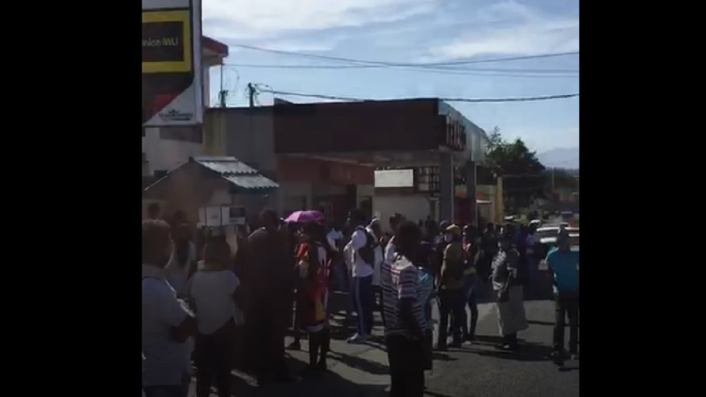 Screenshot of a video showing a huge crowd gathered outside a cambio in St Mary on Monday.