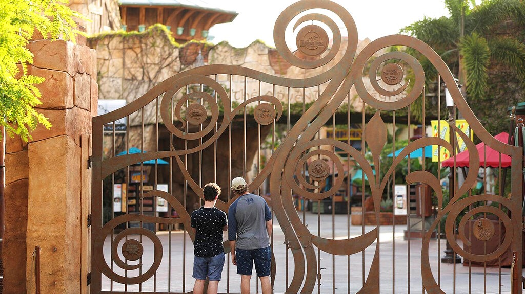 In this Thursday, May 14, 2020, file photo, guests peer through the closed gate to Universal's Islands of Adventure beside Universal CityWalk, in Orlando, Florida. (Stephen M. Dowell/Orlando Sentinel via AP, File)