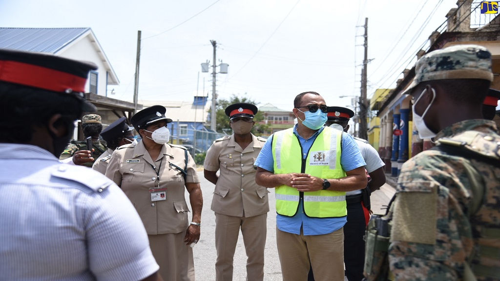 Minister of Health and Wellness, Dr  Christopher Tufton (centre), engaged in one of several meetings with members of the security forces who are manning check-points in sections of St Mary that are under a 14-day quarantine, on Saturday, May 9.