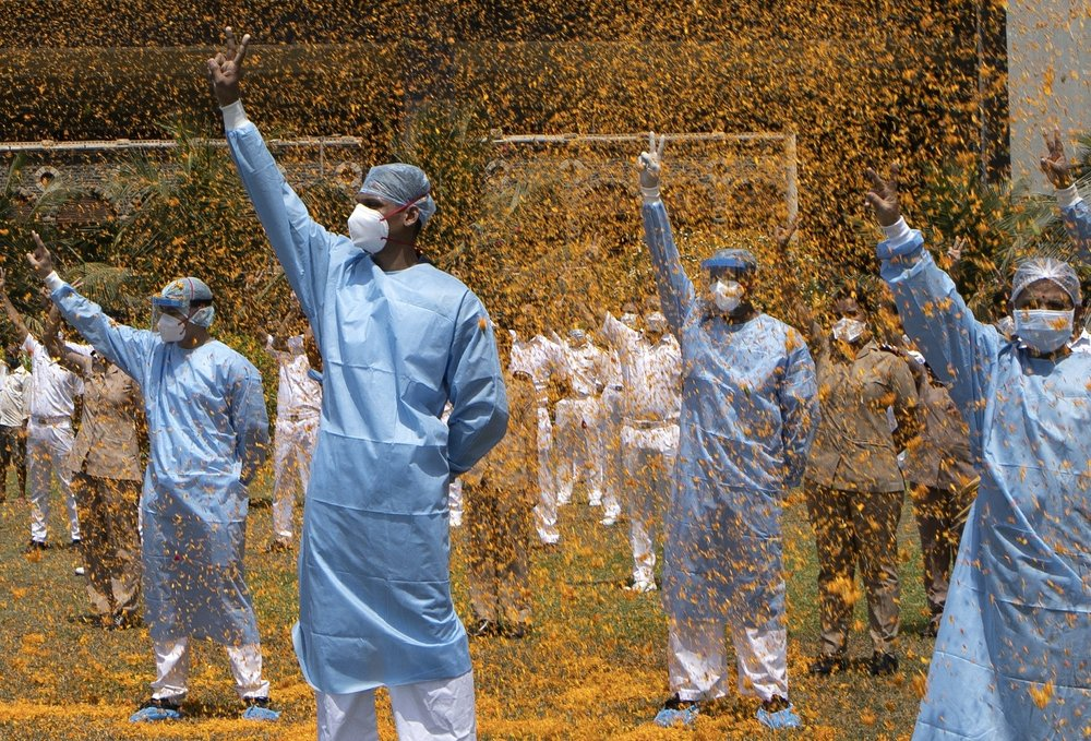 An Indian Air Force helicopter showers flower petals on the staff of INS Asvini hospital in Mumbai, India. The event was part the Armed Forces' efforts to thank the workers, including doctors, nurses and police personnel, who have been at the forefront of the country's battle against the COVID-19 pandemic. (AP Photo/Rajanish Kakade)