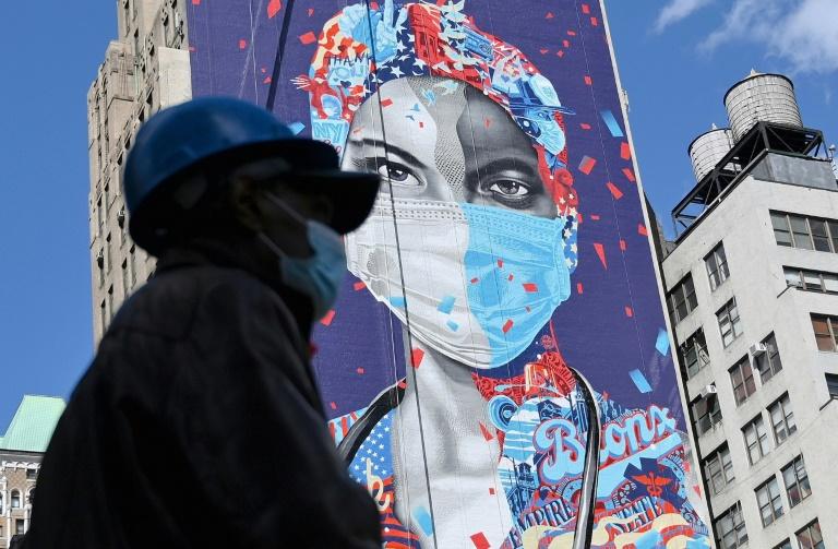 Un ouvrier masqué passe devant une fresque murale en l'honneur des soignants de la pandémie, le 7 mai 2020 à Manhattan