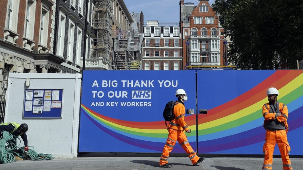 A construction worker passes a sign thanking the NHS in London, as the country in is lockdown to prevent the spread of coronavirus, Thursday, May 7, 2020. The coronavirus has had a dramatic impact on the construction industry. The Bank of England has warned that the British economy could be nearly a third smaller by the end of the first half of this year as a result of the coronavirus pandemic, but also notes the economy could revive quickly. (AP Photo/Kirsty Wigglesworth)
