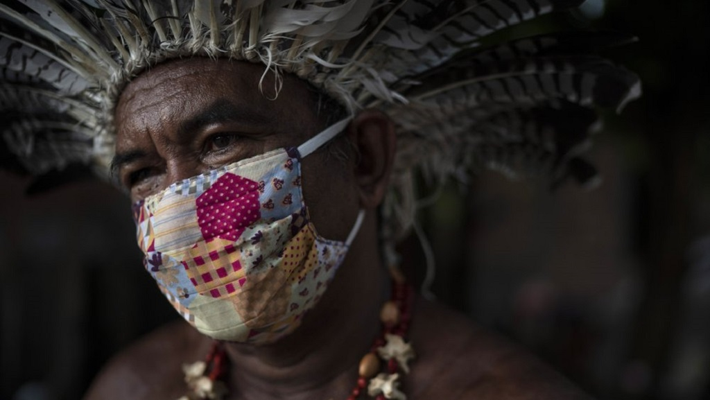 In this May 10, 2020 photo, Pedro dos Santos, the leader of a community named Park of Indigenous Nations, poses for a photo, in Manaus, Brazil. Manaus' lack of the new coronavirus treatment prompted Pedro dos Santos to drink tea made of chicory root, garlic and lime to combat a high fever that lasted 10 days. (AP Photo/Felipe Dana)