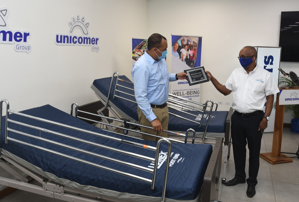 Minister of Health Dr Christopher Tufton (left) receives a plaque from Unicomer Managing Director, Dennis Harris, signifying the date and value of the donation to Jamaica's health system.