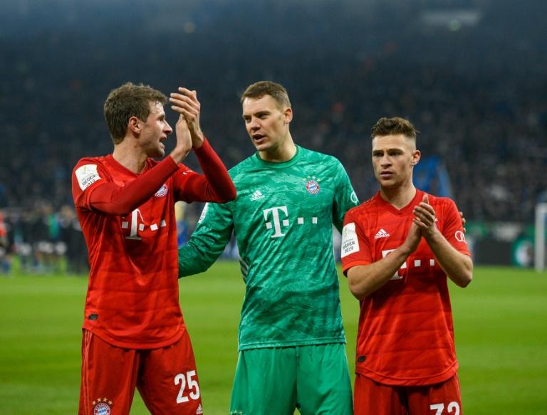 L'attaquant Thomas Müller, le gardien de but Manuel Neuer et le milieu ou défenseur Joshua Kimmich célèbrent leur victoire contre Schalke 04 (1-0) en quart de finale de la Coupe d'Allemagne le 3 mars 2020 à Gelsenkirchen.