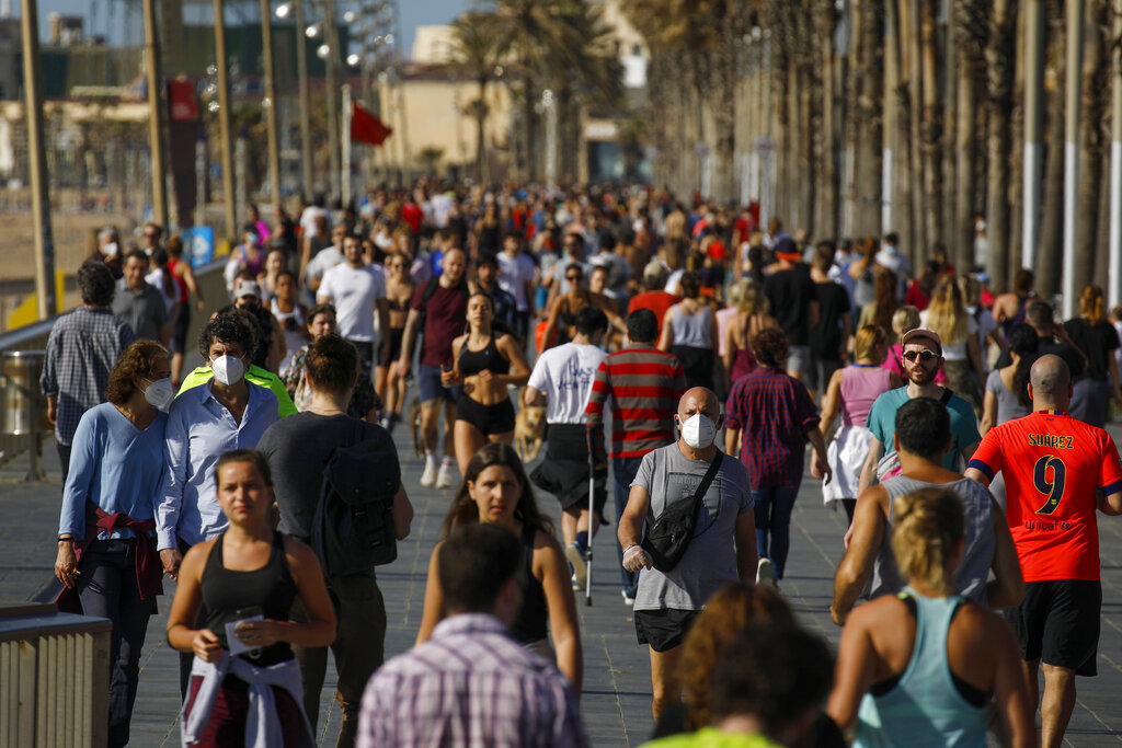 People exercise on a seafront promenade in this photo taken with a telephoto lens in Barcelona, Spain, Saturday, May 2, 2020. Spaniards have filled the streets of the country to do exercise for the first time after seven weeks of confinement in their homes to fight the coronavirus pandemic.