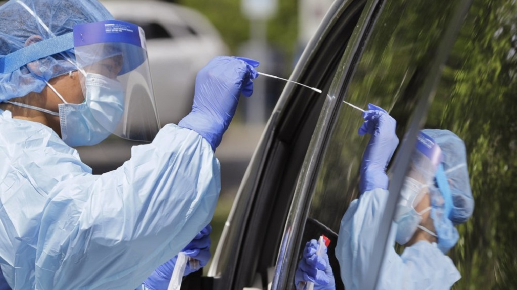 Medical assistant Melanie Zamudio is reflected in the window of a car as she reaches in to take a nasal swab from a driver at a drive-up coronavirus testing site Wednesday, April 29, 2020, in Seattle. (AP Photo/Elaine Thompson)