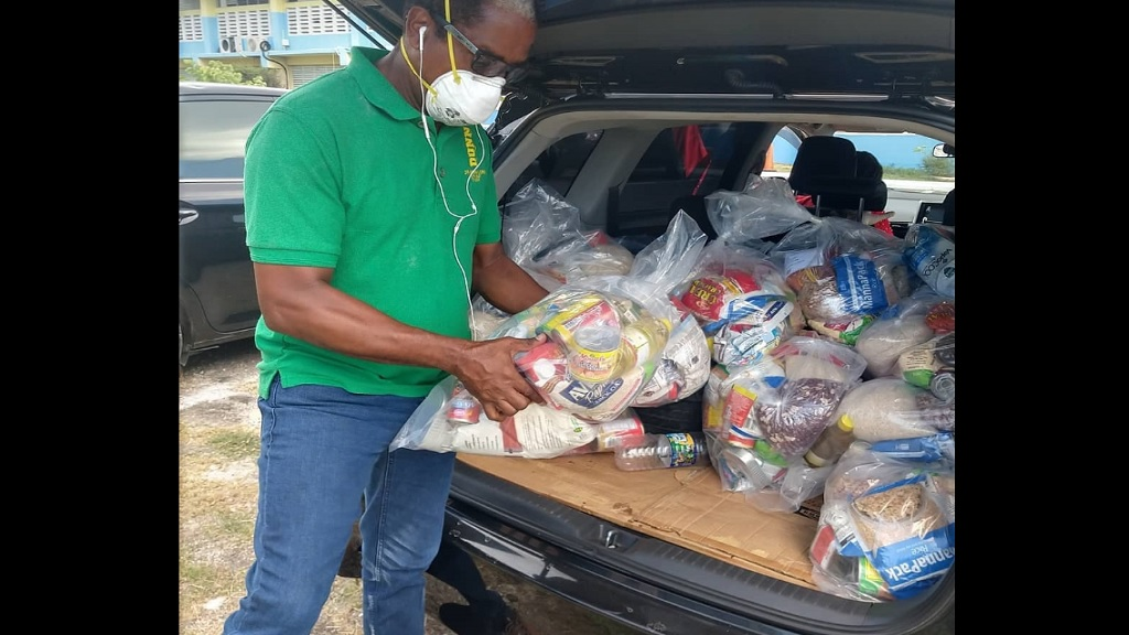 South East St Mary Member of Parliament (MP), Dr Norman Dunn, prepares to distribute food packages in an area under quarantine in the parish.
