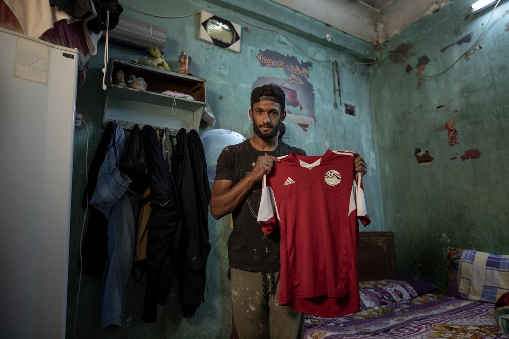 28-year-old defender Mahrous Mahmoud holds up his Egyptian national football team jersey he trains with, inside his home, in Manfalut, a town 350 kilometers (230 miles) south of Cairo in the province of Assiut, Egypt. Mahmoud should be on the field at this time of year playing as a defender for Beni Suef, a club in Egypt's second division. But like millions in the Arab world's most populous country, he has been hit hard by the coronavirus pandemic. (Photos: AP/Nariman El-Mofty)