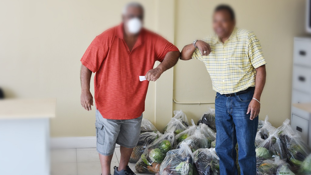 A recipient receives his local food basket and voucher from the Barataria/San Juan constituency office today.