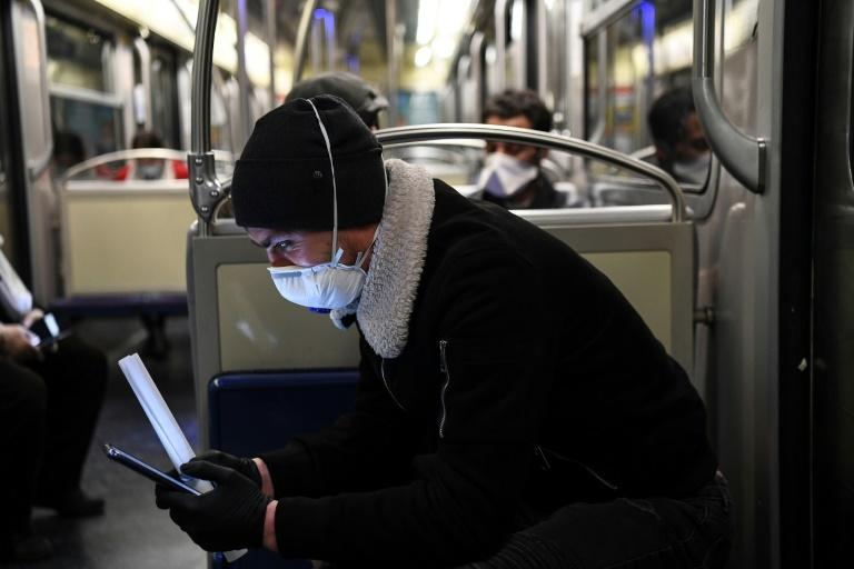 Un homme consulte son smartphone dans le métro, le 23 mars 2020 à Paris afp.com - Alain JOCARD