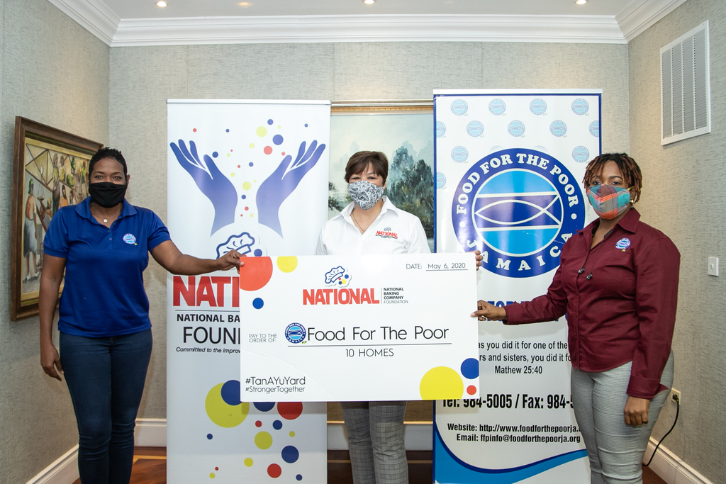 A cheque to the full value of 10 homes is exchanged by (left to right) 