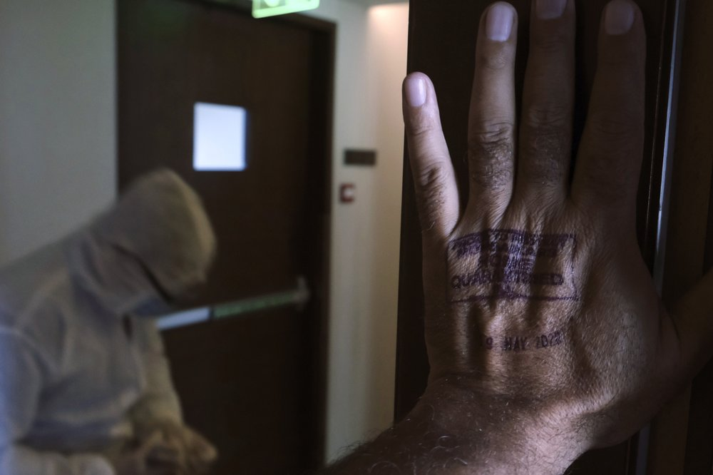 A civic employee puts a stamp on the hand, top right, of a photojournalist in a two-week quarantine after his COVID-19 test report came negative. Associated Press photographer Rafiq Maqbool was among dozens of journalists who tested positive for COVID-19 and then moved collectively to the hotel. On day five of the quarantine, they were tested again, a swab in the nose and mouth. The report showed no sign of the virus. He was to spend the next 14 days in self-isolation at home. (AP Photo/Rafiq Maqbool)