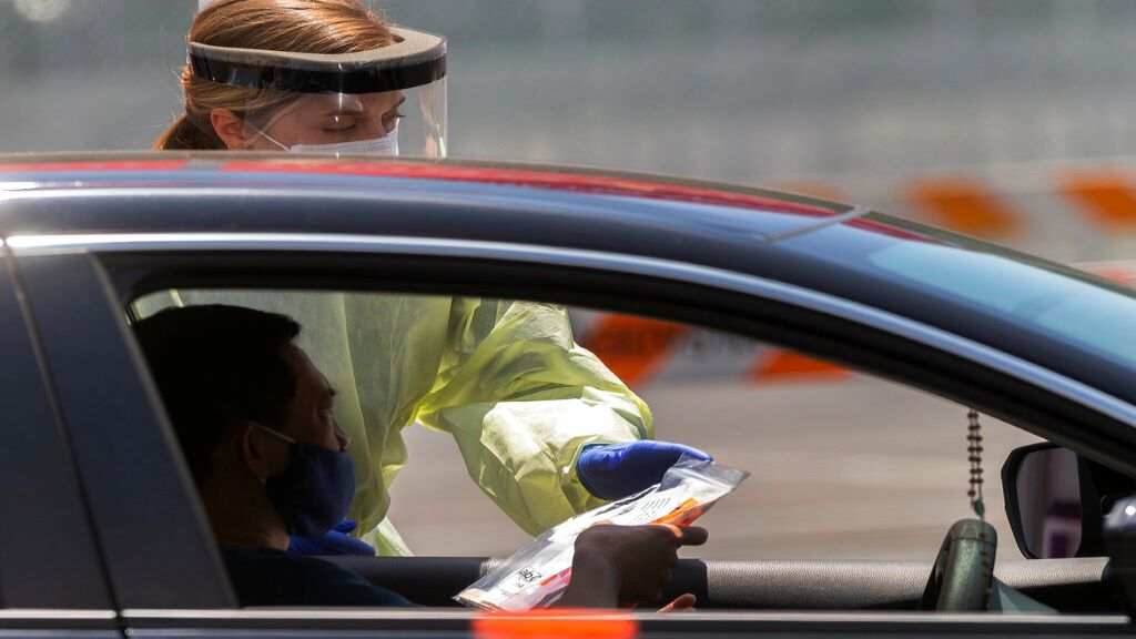 A member of the staff hands over a Covid-19 self test kit to a man at a drive-thru test site at the Rose Bowl in Pasadena, California, Wednesday, May 13, 2020. (AP Photo/Damian Dovarganes)