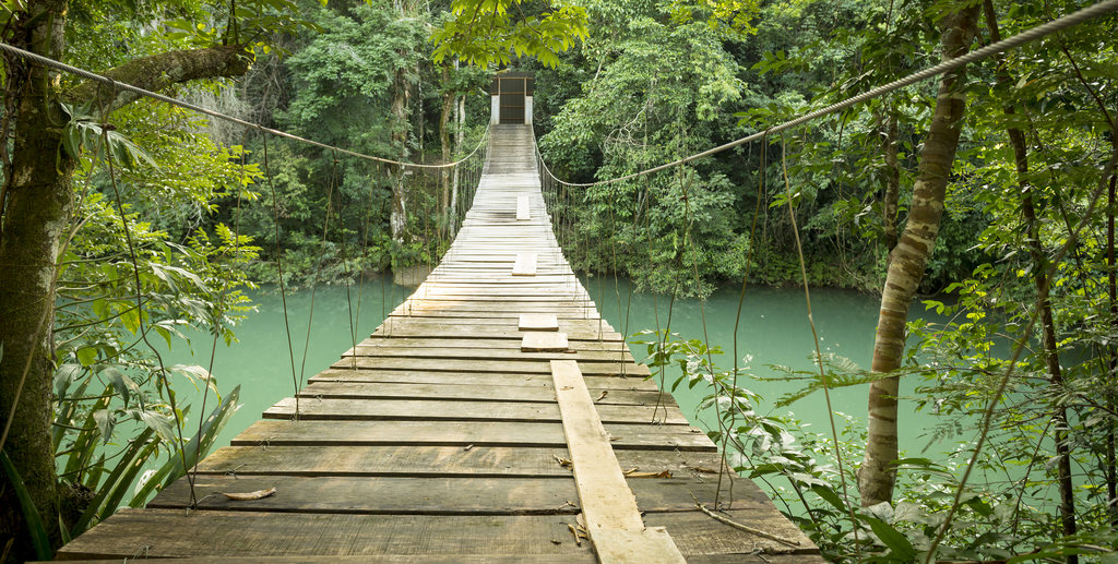 Hanging bridge over river in jungle of Rio Blanco National Park in Toledo Belize. GettyImages