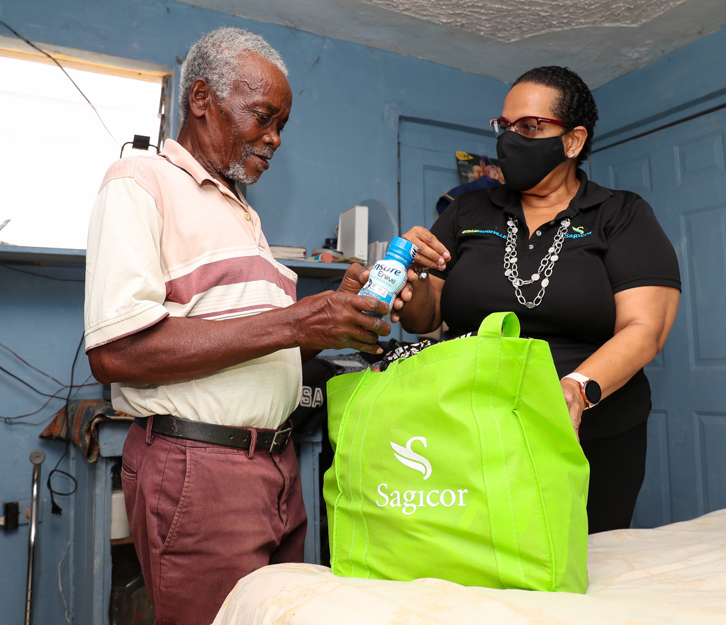 Charles Frater of New Green, Mandeville, looks at items donated by Dale Greaves Smith (right), Senior Branch Manager, Sagicor Life, Mandeville, during a visit to his home.