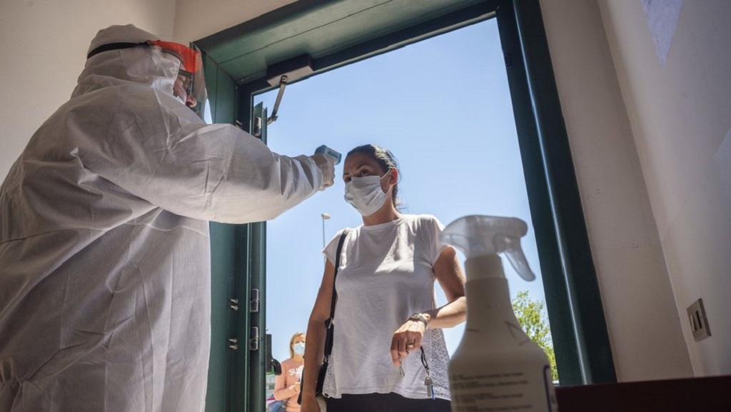 A worker of the Calzaturificio M.G.T shoe factory in Castelnuovo Vomano, central Italy, has her temperature checked at the entrance of the factory when she returns to work, Monday, May 4, 2020. Italy began stirring again Monday after a two-month coronavirus shutdown, with 4.4 million Italians able to return to work and restrictions on movement eased in the first European country to lock down in a bid to stem COVID-19 infections. (AP Photo/Domenico Stinellis)