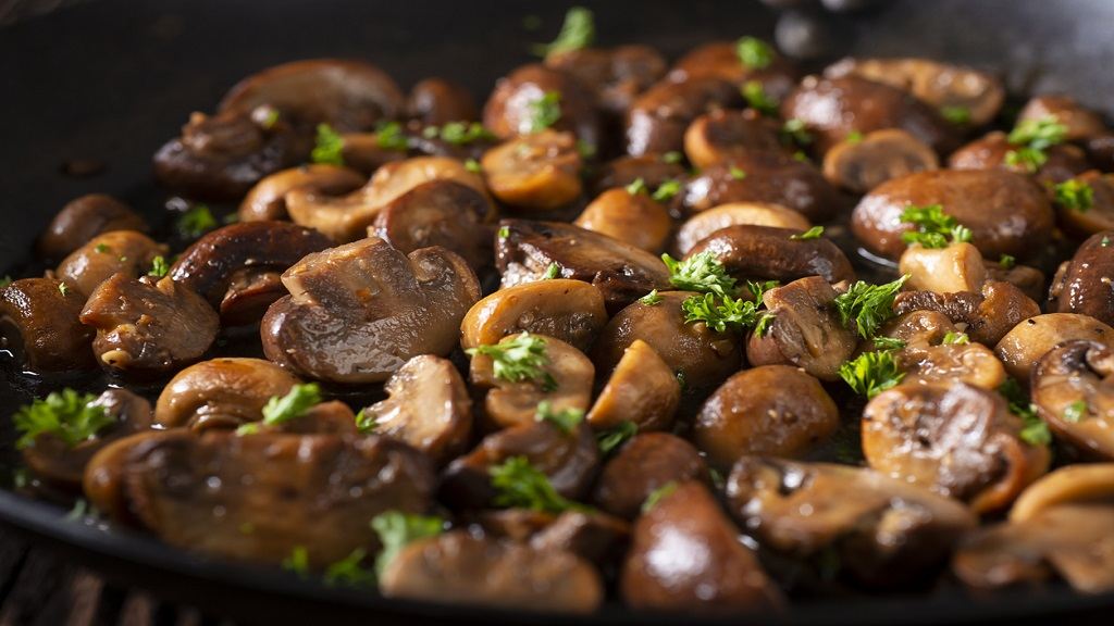 iStock photo of mushrooms sautéed in a carbon steel skillet.