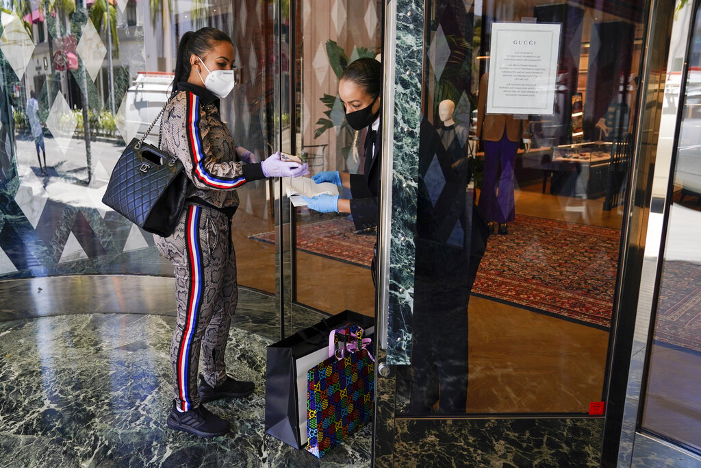 Delicia Cordon receives a purchase from a salesperson at Gucci on Rodeo Drive Tuesday, May 19, 2020, in Beverly Hills, California. (AP Photo/Ashley Landis)